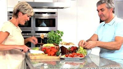stock-footage-mature-couple-in-home-kitchen-preparing-lunch