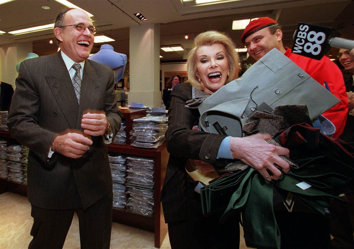 Joan Rivers with the New York City Mayor Rudolph Giuliani. She was carrying a pile of clothing to a cash register at Macy's to kick off the start of the elimination of sales tax on clothing